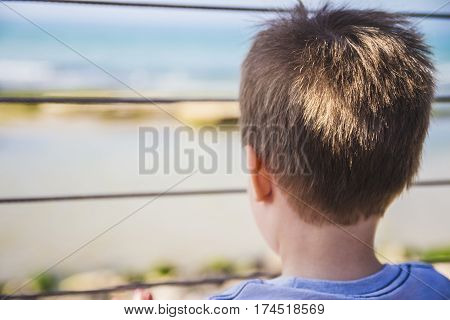 Young Boy Looks Far Away To The Horizon From Behind Metal Fence