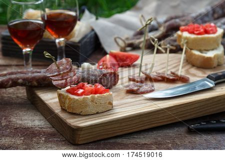 Bread, Sausage, Red Wine, Glass, Cutting Board And Knife Arranged On A Wooden Table For A Snack In T