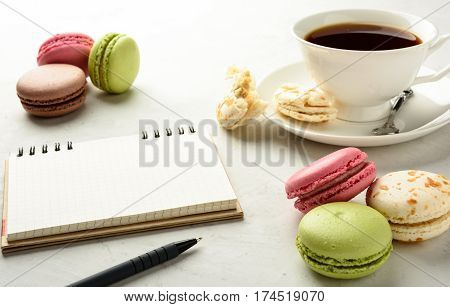 Cup of black tea with tasty varicolored macaroons and notebook on a white background in light key. Copy space.