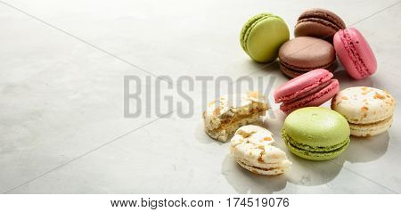 Varicolored macaroons on a white background in light key. Copy space.