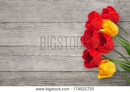 Beautiful Wooden background with Red and yellow tulips flowers. Colorful Greeting Card for Mother's Day Birthday March 8. Horizontal Image With Copy Space