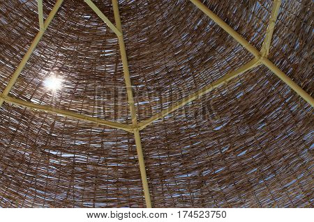 a sight at the sun shining in blue sky through the wooden sunshade on a resort