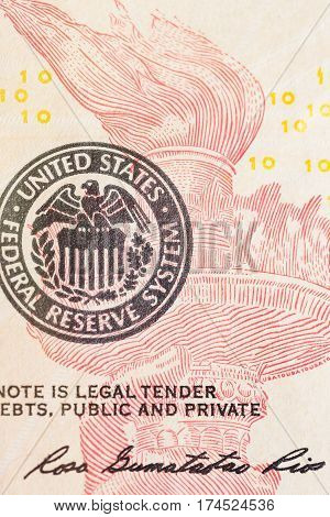 United States Federal Reserve System symbol with torch from ten dollar bank note. Close up shot.