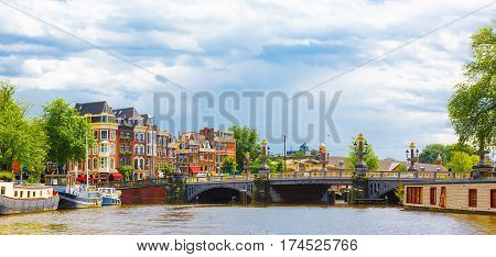 Beautiful panoramic cityscape of Amsterdam capital of Netherlands. Colorful view of the Amstel canal with an amazing Blauwbrug Blue Bridge in summer Sunny day. Horizontal Image