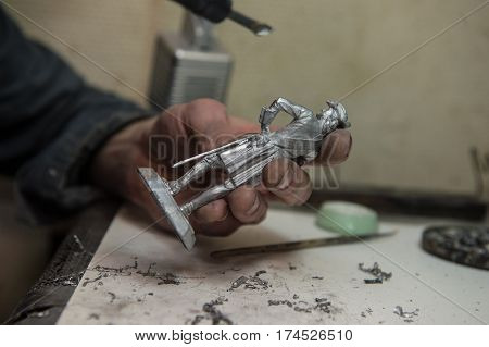 Saint-Petersburg Russia - February 21 2017: A small factory producing small batches pewter figurines. Master with a soldering iron removes blemishes after casting