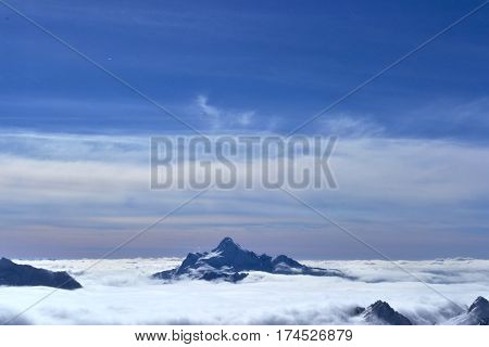 lonely mountain in the clouds on the horizon. beautiful mountain landscape with clouds, blue sky, snow peak.