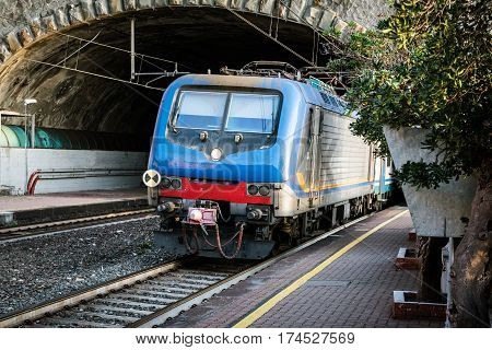 Passenger train driving out from tunnel near Riomaggiore town, Cinque Terre, Italy