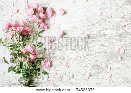 pink rose flowers bouquet mockup on white rustic wooden background for creative work design. top view. vintage toning