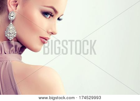 Beautiful girl with evening makeup with large earrings jewelry .