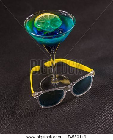 colored drink a combination of blue and green lemon martini glass yellow sunglasses party set