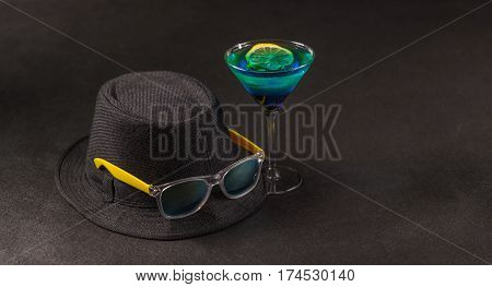 colored drink a combination of blue and green lemon martini glass yellow sunglasses a black hat party set