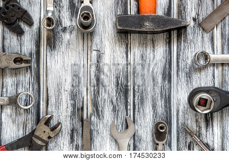 Tools frame on a wooden table. Tools for DIY on a black and white wooden background.
