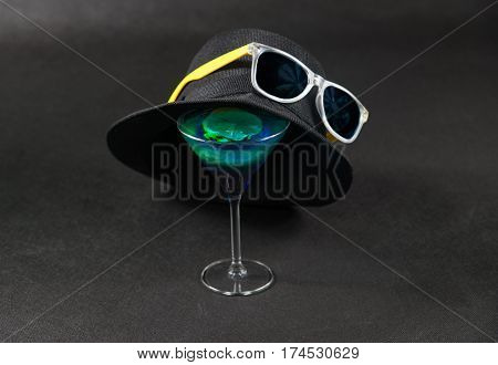colored drink a combination of blue and green lemon martini glass yellow sunglasses a black hat on the glass party set