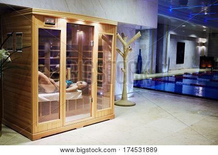 MOSCOW, RUSSIA - NOV 14, 2015: Woman in swimsuit lies on bench in infrared sauna cabin behind glass doors in recreational area in Radisson Royal Ukraine hotel, one of seven Stalin skyscrapers.