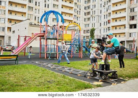 MOSCOW, RUSSIA - JUN 27, 2016: Cameraman and assistants shoot reportage from children playground in courtyard of residential houses.