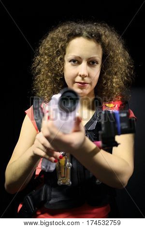 MOSCOW - DEC 13, 2014: Woman with curly hair in a special vest with a laser gun in laser tag at the shopping center Capitol Vernadsky