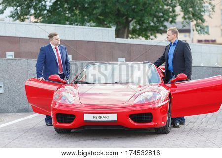 MOSCOW, RUSSIA - JUN 22, 2016: Two young businessman (with model releases) going to take ride on red luxury supercar Ferrari