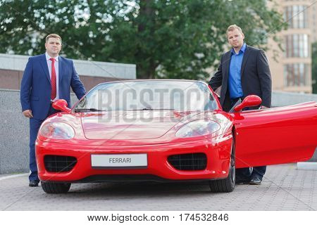 MOSCOW, RUSSIA - JUN 22, 2016: two mature business people outside standing next to luxury supercar Ferrari