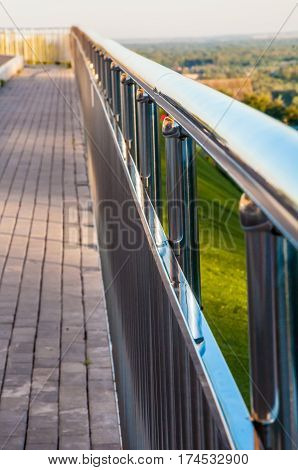Path with metal railings and covered by gray concrete blocks