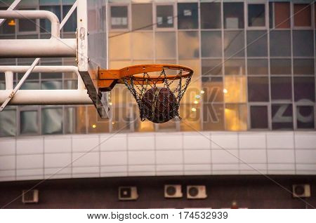 A basketball hoop with a ball inside on the background of the city