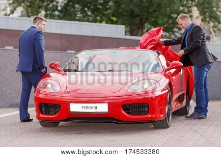 MOSCOW, RUSSIA - JUN 22, 2016: Two successful businessman  going to take ride on red luxury supercar Ferrari
