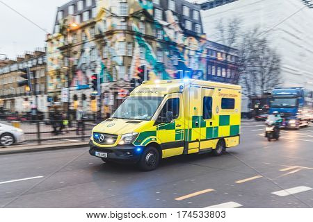 LONDON UK - MARCH 1 2017: Emergency ambulance rushing on the street with emergency lights flashing in London city centre