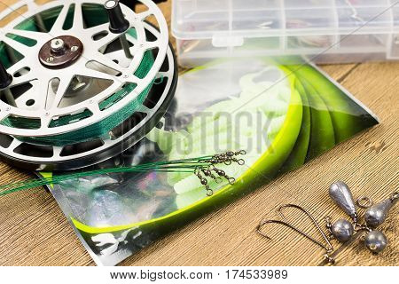 fishin acsessories and old reel on the wooden table