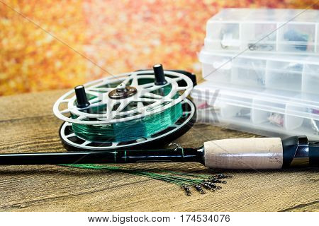 fishing spinning leashes with reel and rod on the wooden table at autumn background
