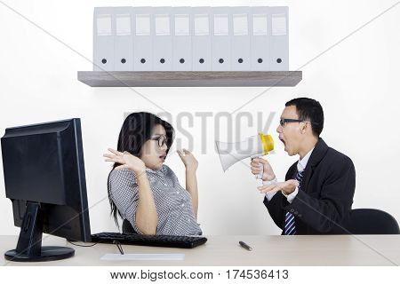 Male manager is screaming at his secretary through megaphone while working with a computer in the office room