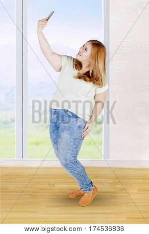 Beautiful overweight woman with blonde hair taking selfie photo with her smartphone at home
