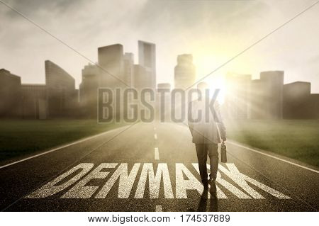 Young businessman holding a briefcase and walking above Denmark word on the road