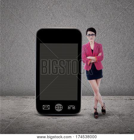 Businesswoman standing next to smartphone on grey