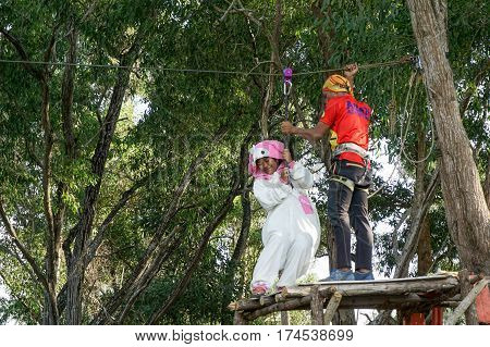 Labuan,Malaysia-Feb 12,2017:Happy girl in teddy bear costume enjoying on a zipline in Labuan,Malaysia.There will be more ziplines in Malaysia,especially when there have so much natural resources & rainforest.