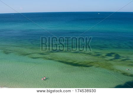 Panama City Beach Florida Blue Green Ocean Water with Pink Inner Tubes Floating