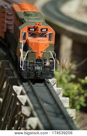 G Scale  Orange and Green Railroad Model Train Running On Trestle Track