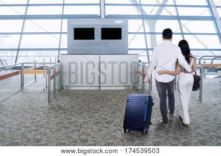 Rear view of two young couple carrying a luggage while walking in the airport terminal