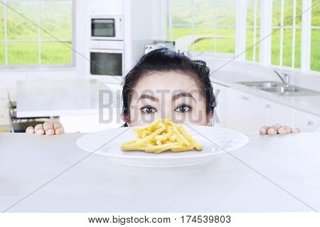 Picture of fat woman peeping french fries on a plate in the kitchen