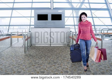 Beautiful female passenger walking in the airport terminal while wearing sweater and carrying a luggage with shopping bags