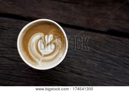 cappuccino coffee in takeaway cup on wooden table