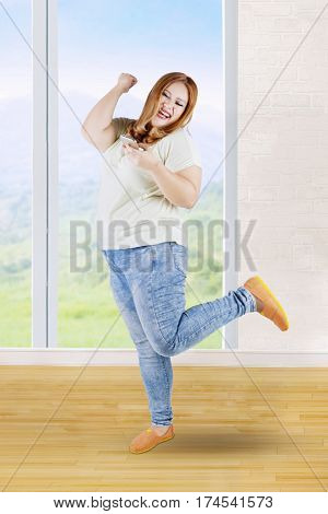 Portrait of happy overweight woman with blonde hair reading sms message on her mobile phone at home