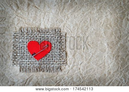Heart attached on canvas with safety pin grunge paper background