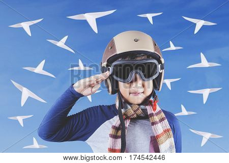 Portrait of a little male aviator showing a saluting gesture while wearing an aviator helmet with paper planes shot outdoors