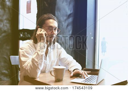 Businessman talking bu mobile phone with opened laptop in cafe co-working space. Having coffee-break