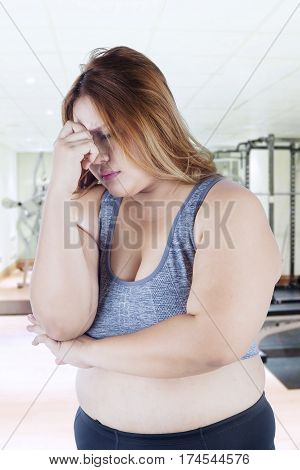 Portrait of overweight woman standing in the fitness center and looks stressful