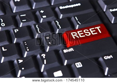 Close up of red button with text of reset on the computer keyboard