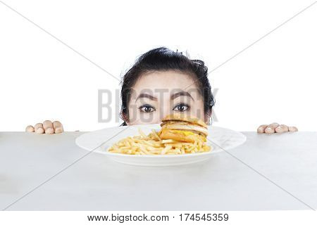 Image of young female is peeping hamburger on the table isolated on white background