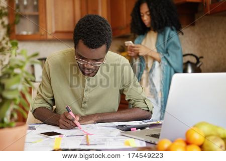 Indoor Shot Of Dark-skinned Man Sitting At Kitchen Table Using Pink Felt Pen, Making Notes In Papers