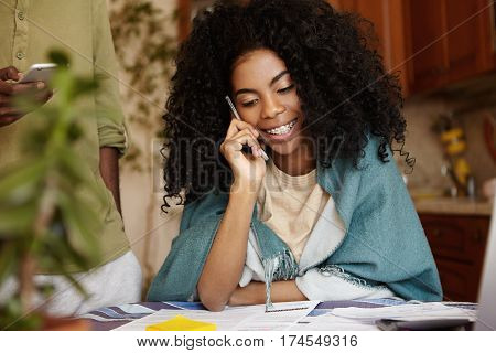 Indoor Portrait Of Attractive Young Dark-skinned Female With Curly Hairstyle Having Phone Conversati