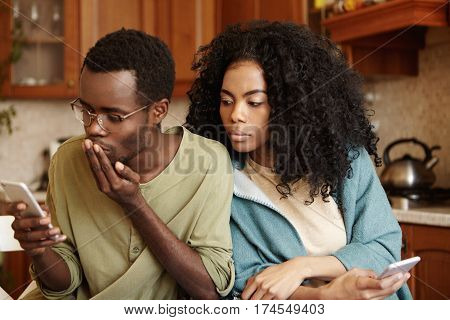 Handsome African-american Male In Glasses Reading Sms On Mobile Phone, Messaging Lover While His Pos