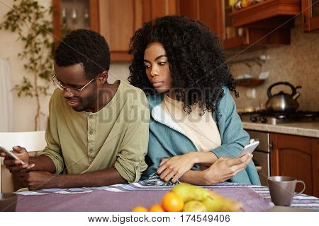 Portrait Of Sneaky And Jealous Young African Wife Spying On Her Husband, Looking Over Shoulder, Tryi